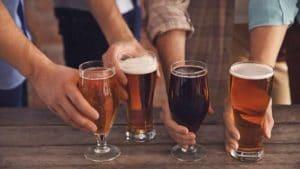 Männergruppe hält dunkles und helles Bier auf dem Holztisch