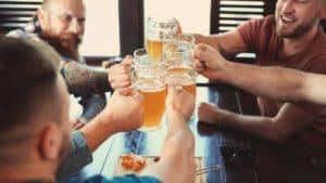 Freunde prosten mit Bier in einer Bar