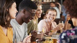 Eine Gruppe Freunde trifft sich in einer Bar und trinkt gemeinsam