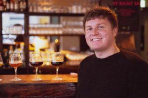Bierexperte vor Glaesern auf der Theke