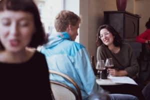 Frau in der Bar, mit Fokuz auf den dahinterliegenden Pärchentisch