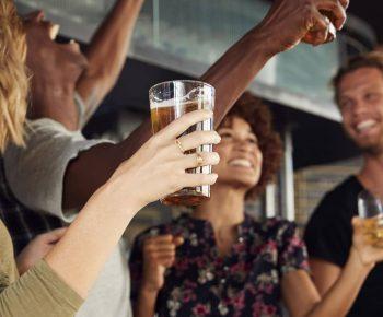 Gruppe Frauen und Männer feiern in einer Sportsbar zusammen